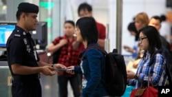 3月9日马里西亚警察在吉隆坡的国际机场检查旅客的身份证明