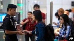 ប៉ូលិសម៉ាលេស៊ីពិនិត្យឯកសារអត្តសញ្ញាណអ្នកដំណើរនៅអាកាសយានដ្ឋានអន្តរជាតិ Kuala Lumpur International Airport កាលពីថ្ងៃទី៩ខែមីនាឆ្នាំ២០១៤។