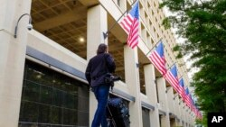 FILE - A member of the news media walks in front of the FBI headquarters building in Washington, May 10, 2017.