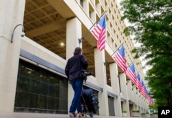 FILE - A person walks in front of the FBI headquarters building in Washington, May 10, 2017.