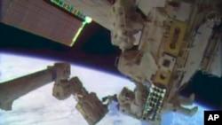 從美國太空總署發佈的畫面中顯示﹐兩名美國宇航員馬斯特拉齊奧(上)和霍普金斯進行太空行走修復國際空間站的一個關鍵冷卻系統。