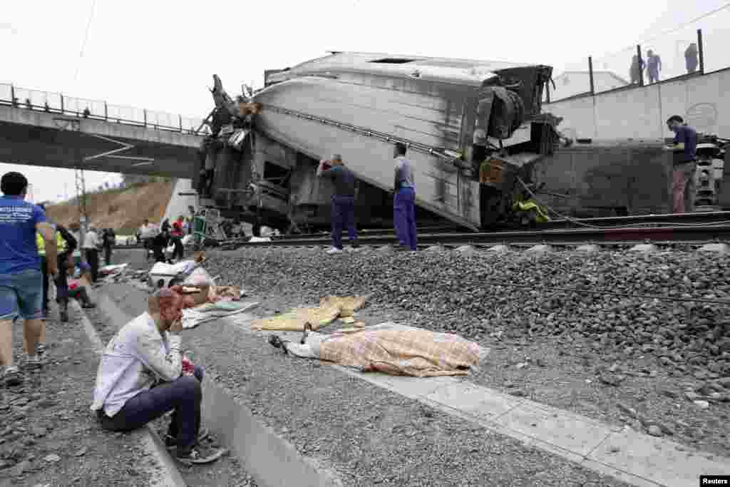 Xác các nạn nhân được che phủ dọc theo đường rầy gần những thanh sắt cong vẹo của các toa xe sau vụ tai nạn.
