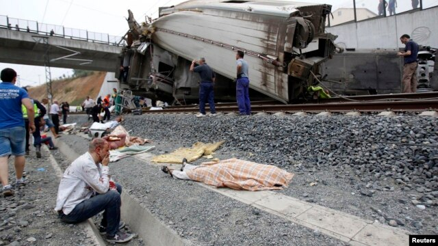 A wounded victim sits next to a body covered with a blanket after a train crashed near Santiago de Compostela, northwestern Spain, July 24, 2013.