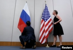 FILE - Staffers install U.S. and Russian flags as part of a bilateral meeting, Aug. 26, 2016. Theoretically, U.S. President Donald Trump and Russian President Vladimir Putin would have an opportunity to meet Friday in Vietnam but it's not clear whether substantive talks will be scheduled.