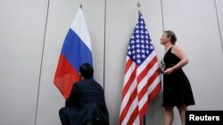 FILE - Staffers install U.S. and Russian flags as part of a bilateral meeting, Aug. 26, 2016. Theoretically, U.S. President Donald Trump and Russian President Vladimir Putin would have an opportunity to meet Friday in Vietnam but it's not clear whether the two will talk face-to-face.