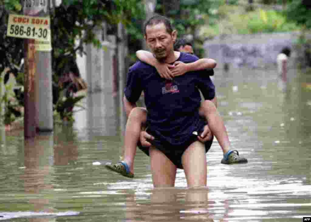 An Indonesian man carries his son through a flooded neighborhood in Tangerang on the outskirts of Jakarta, Indonesia, Wednesday, Oct. 27, 2010. (AP Photo/Tatan Syuflana)