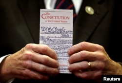 FILE - A member of Congress holds a copy of the U.S. Constitution during a press conference held to outline the claim that U.S. President Donald Trump violated the emoluments clause of the Constitution in the U.S. Capitol in Washington June 20, 2017.