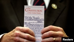 FILE - A member of Congress holds a copy of the U.S. Constitution in Washington, June 20, 2017.