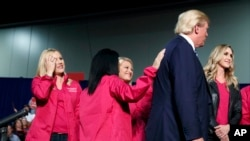 Republican presidential candidate Donald Trump stands on stage with female supporters during a campaign rally in Charlotte, North Carolina, Oct. 14, 2016.