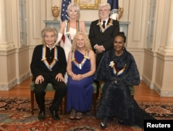 Kennedy Center Honorees (L-R, standing) actress and singer Rita Moreno, filmmaker George Lucas, (L-R, seated) Japanese conductor Seiji Ozawa, singer-songwriter Carole King and actress Cicely Tyson gather for a group photo after a gala dinner at the U.S. State Department in Washington, Dec. 5, 2015.