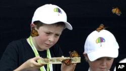 Cameron Lucas (L) and Tyler Bishop-Ward release some of the 185 butterflies during a memorial service in Christchurch February 22, 2012, to mark the 1st anniversary of the earthquake in Christchurch which killed 185 people.