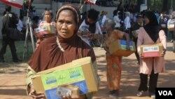 Para warga menerima paket sembako lebaran yang dibagikan oleh berbagai ormas lintas agama dan etnis di Solo, Minggu 12/8 (foto: Yudha Satriawan/VOA).