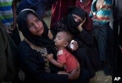 22일 방글라데시 콕스 바자르 외곽의 쿠투팔롱 난민촌에서 로힝야족 난민 여성이 아이를 안고 구호물품을 기다리고 있다.