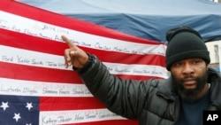 Jamine Clark menunjuk nama abangnya, Jamar Clark, pada bendera AS terbalik yang bertuliskan nama orang-orang yang mati di tangan polisi, di luar kantor polisi Minneapolis (17/11). (AP/Jim Mone)