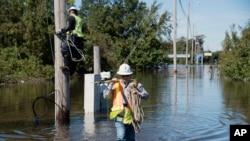 Dua pekerja berusaha memperbaiki jaringan listrik yang rusak akibat badai Matthew melanda Lumberton, North Carolina, Selasa (11/10).