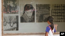 FILE - A Cambodian girl looks at images of Khmer Rouge victims at Tuol Sleng genocide museum, formerly the regime's notorious S-21 prison in Phnom Penh, Cambodia, March 26, 2015.
