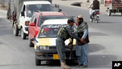 An Afghan policeman searches a passenger at a checkpoint in Kandahar, Jan. 26, 2016.