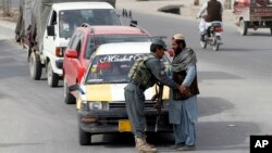 FILE - An Afghan policeman searches a passenger at a checkpoint in Kandahar, Afghanistan, Jan. 26, 2016. Four Afghan policemen were killed and another seven wounded when one of their colleagues opened fire on them in the volatile southern province of Kandahar.