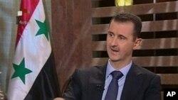ຮູບພາບ ປ. Bashar al-Assad ແຫ່ງຊີເຣຍໃນຈໍໂທລະພາບແຫ່ງ ຊາດຂອງຊີເຣຍເວລາໃຫ້ສໍາພາດຕໍ່ນັກຂ່າວ ວັນທີ 21 ສິງຫາ 2011