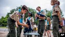 Pramuka putri dari Scouts BSA Troop 19 di Austin, Texas, melipat bendera untuk sebuah upacara bendera, di Austin, Texas, 4 Juni 2019. (Foto: Anthony Smith/The Boy Scouts of America via AP Images)