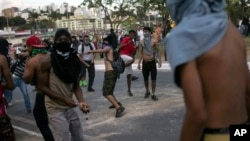 Demonstrators throw at police officers outside Mineirao stadium during Confederations Cup semifinal match between Brazil and Uruguay, Belo Horizonte, June 26, 2013.