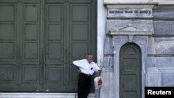 Seorang pensiunan menunggu di luar kantor cabang National Bank yang tutup di Athena (29/6). (Reuters/Alkis Konstantinidis)