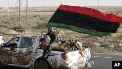 리비아 왕정국기를 매단 시민군 차량이 동부 라스라누프와 무아마르 카다피 국가원수의 고향인 시르테를 잇는 도로를 달리고 있다.