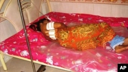 An unidentified garment worker lying on a hospital bed with multiple gunshot wounds to her back. The police identified the mayor of Bavet town, Chhouk Bandit, as the prime suspect.