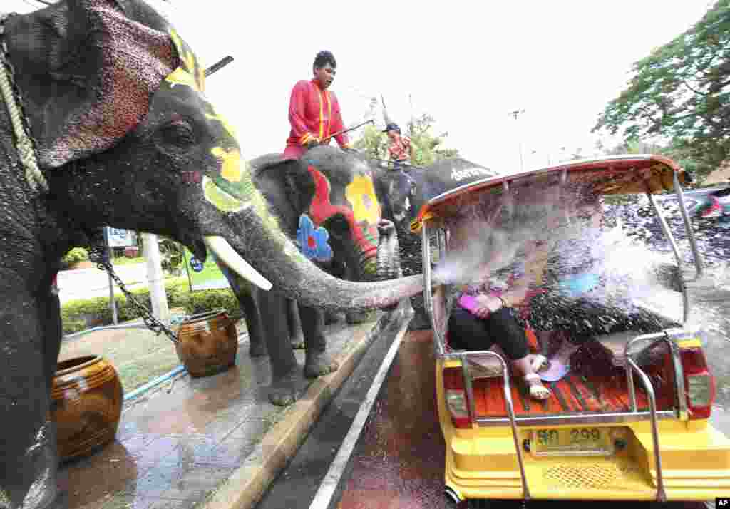 An elephant blows water from its trunk onto tourists in a motor-tricycle, or Tuk Tuk, ahead of the Buddhist New Year, known as Songkran, in Ayutthaya province, central Thailand.