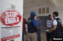 Các thành viên Tổ chức Y tế Thế giới và các giám đốc y tế đứng bên ngoài bệnh viện quận Port Loko, nơi khoa phụ sản đã được biến thành trung tâm cách ly cho những người bị nghi nhiễm Ebola.