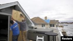 Warga di Milford, negara bagian Connecticut melindungi kaca-kaca di rumahnya dengan triplek untuk antisipasi datangnya badai super 'Sandy' (28/10).