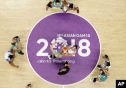 India's Rajapriyadharshini Rajaganapathi, right, jumps against Kazakhstan's Nadezhda Kondrakova during their women's basketball match at the 18th Asian Games in Jakarta, Indonesia, Aug. 17, 2018.