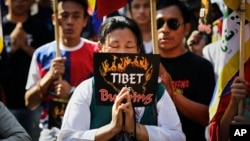 FILE - Exiled Tibetans pray during a protest rally to express solidarity with Tibetans who have self-immolated, in New Delhi, India, Nov. 28, 2012.