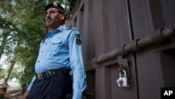 A Pakistani police officer stands guard outside a sealed Save the Children office in Islamabad, Pakistan, June 12, 2015.