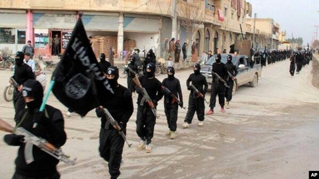 FILE - Fighters from the al-Qaida linked Islamic State of Iraq and the Levant (ISIL) marching in Raqqa, Syria.