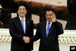 រូបឯកសារ៖ លោកនាយករដ្ឋមន្ត្រី ហ៊ុន សែន (ស្តាំ) ចាប់ដៃគ្នាជាមួយលោកនាយករដ្ឋមន្ត្រីជប៉ុន Shinzo Abe (ឆ្វេង) នៅក្នុងវិមានសន្តិភាព នៅរាជធានីភ្នំពេញ កាលពីថ្ងៃសៅរ៍ ទី១៦ ខែវិច្ឆិកា ឆ្នាំ២០១៣។