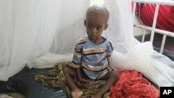一名营养不良的索马里儿童8月1日坐在摩加迪沙一所医院的病床上