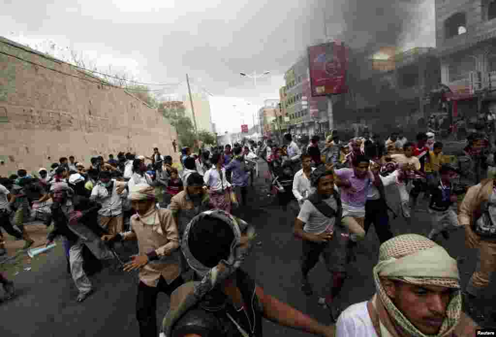 Anti-Houthi protesters run as pro-Houthi police troopers open fire in the air to disperse them in Yemen's southwestern city of Taiz, March 23, 2015.