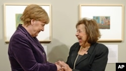 """Artist Nelly Toll (r) shares a light moment with German Chancellor Angela Merkel as Merkel inaugurates the exhibition """"Art from the Holocaust - 100 works from the Yad Vashem collection"""" in the German Historical Museum in Berlin, Jan. 25, 2016."""