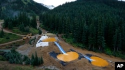 FILE - Water flows through a series of retention ponds built to contain and filter out heavy metals and chemicals from the Gold King mine chemical accident, in the spillway about 1/4 mile downstream from the mine, outside Silverton, Colorado, Aug. 12, 201
