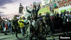 A reveler blows a whistle as he takes part in the National Carnival 2015 annual parade in Port-au-Prince, Feb. 15, 2015.
