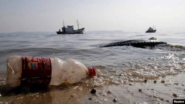 A plastic bottle and a tire are seen near a fishing boat on Fundao beach in the Guanabara Bay in Rio de Janeiro, March 13, 2014.