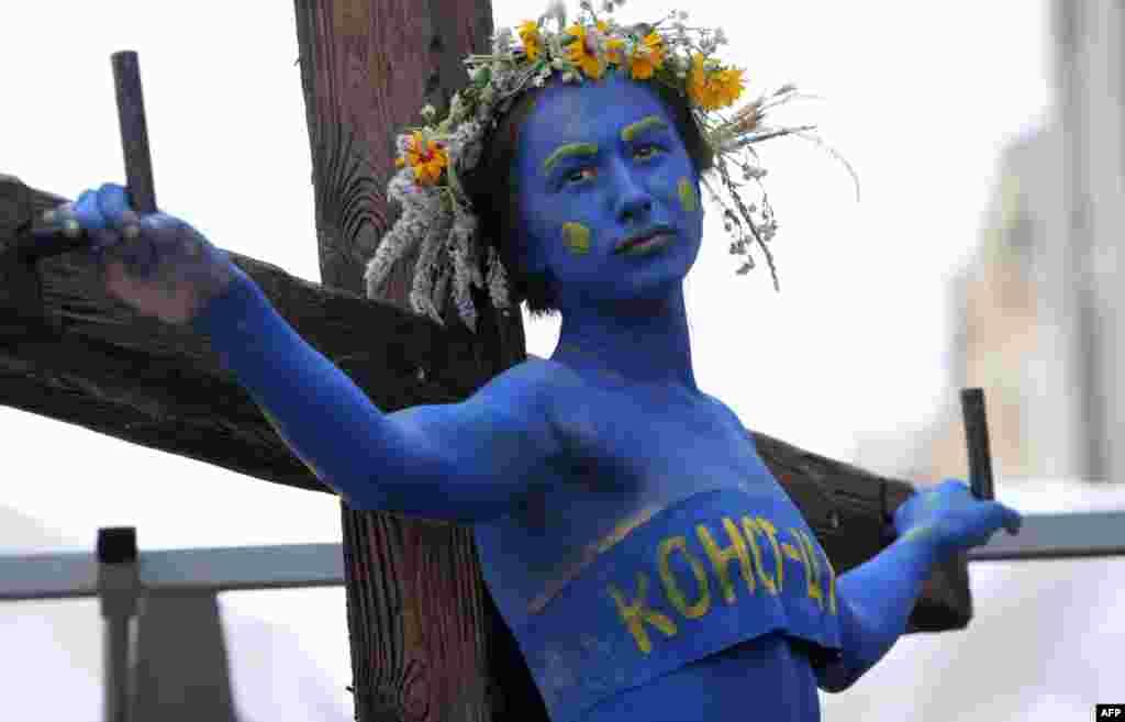 """Một cô gái biểu tượng của Hiến pháp Ukraina """"bị đóng đinh trên cây thập tự."""" Những người hoạt động kêu gọi nhân dân Ukraina hành động để bảo vệ Hiến Pháp trước ngày Hiến Pháp được tổ chức vào 28-6."""