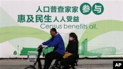 A man and woman ride an electric bicycle past a publicity board for the 6th China Census in Beijing Monday, Nov. 1, 2010. China kicked off its once-a-decade census Monday, a whirlwind 10-day head count that will see 6 million census takers go door-to-door