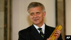 Marek Belka, governor of the Central Bank of Poland, holds gold at bank headquarters, Warsaw, June 17, 2011.