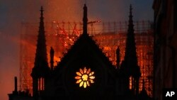 Flames and smoke rise from Notre Dame cathedral as it burns in Paris, Monday, April 15, 2019. Massive plumes of yellow brown smoke is filling the air above Notre Dame Cathedral and ash is falling on tourists and others around the island that marks the center of Paris. (AP Photo/T