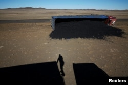 A photographer casts his shadow near a coal truck that flipped over at Khanbogd Soum, near the border with China in the Gobi desert, Mongolia, Oct. 29, 2017. Getting to the border can be a harrowing ordeal, as vehicles speed toward China and back down a one-lane road.