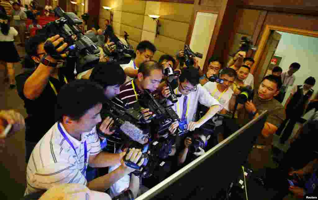 Journalists film a screen displaying a court's microblog page showing disgraced Chinese politician Bo Xilai standing trial, in Jinan, Shandong province. Bo appeared in public for the first time in more than a year to face trial in eastern China, the final chapter of the country's most politically charged case in more than three decades.