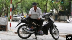 Nguyen Kim Lan reads a newspaper as he waits for customers at an intersection in Hanoi, Vietnam, June 21, 2017. Lan, 62-year-old traditional motorbike taxi driver, or Xe Om, used to make a decent living shuttling customers, but his clientele has dwindled as young and tech-savvy Vietnamese increasingly use ride-hailing apps.