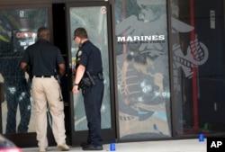 Cảnh sát đi vào trung tâm tuyển binh qua những cánh cửa đầy lỗ đạn ở Chattanooga, Tennessee, ngày 16 tháng 7, 2015.